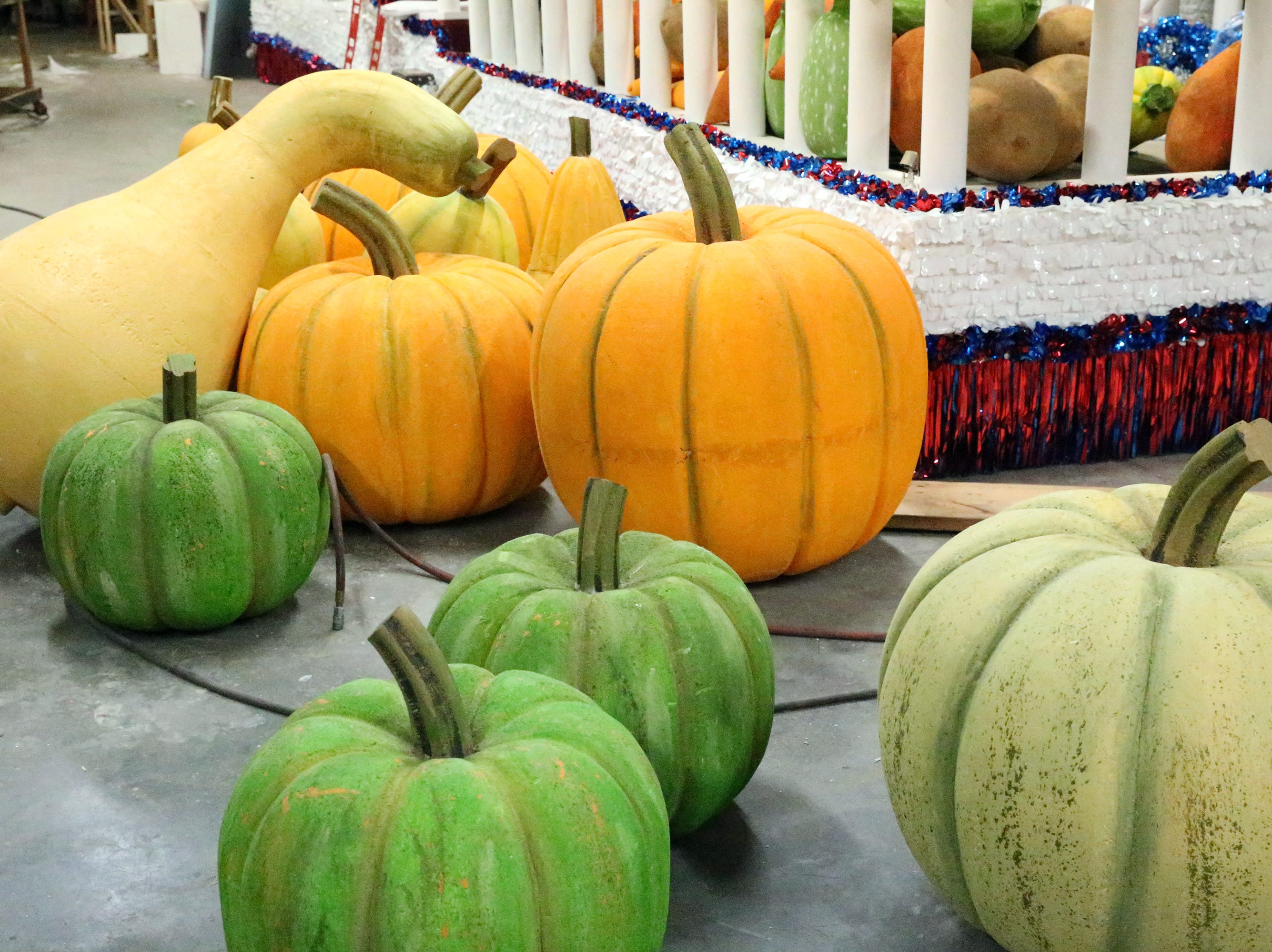 Fruits and vegetables of different sizes are fashioned out of styrofoam to be put as part of a cornucopia on a parade float.