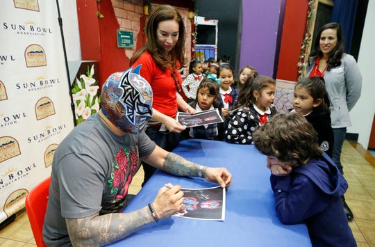 El Paso WWE Superstar Sin Cara signs autographs for students at the La Fe Community Center. Sin Cara is the 2018 grand marshal of the FirstLight Federal Credit Union Sun Bowl Parade on Thanksgiving Day.