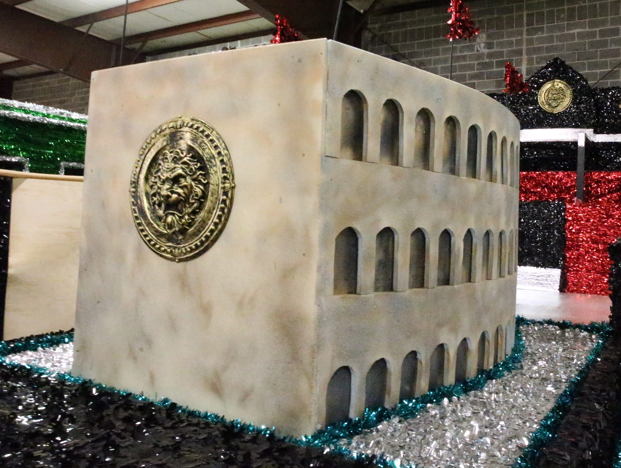 The Roman Coliseum is depicted in a parade float.