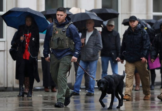 "A K-9 team walks past people waiting to enter Brooklyn federal court on Tuesday, Nov. 13, 2018, in New York. Opening statements at the trial of the notorious Mexican drug lord Joaquin ""El Chapo"" Guzman were set to begin Tuesday morning under tight security. The evidence will include the testimony of more than a dozen cooperating witnesses who prosecutors say are risking retribution by taking the stand."