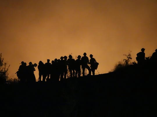 Firefighters gather on a ridge above Coyote Hills Park in Simi Valley during the Woolsey Fire. Senate Bill 542 would retroactively apply back to 2017 and 2018, the height of wildfire destruction in California.