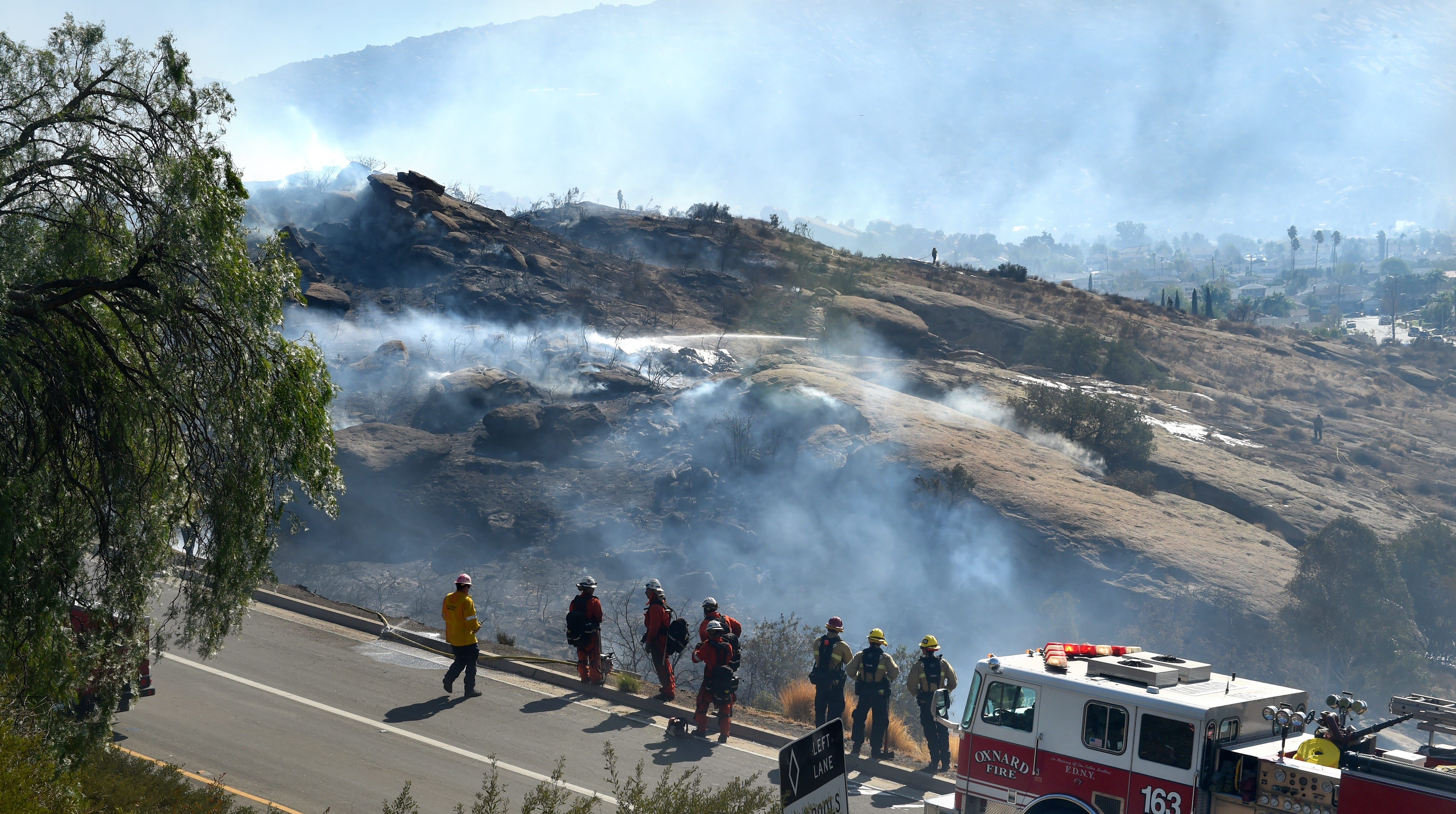 Firefighters watch as smoke rises over the hills along Highway 118 in Simi Valley, where a brushfire threatened several structures as it burned nearly 100 acres on Monday.