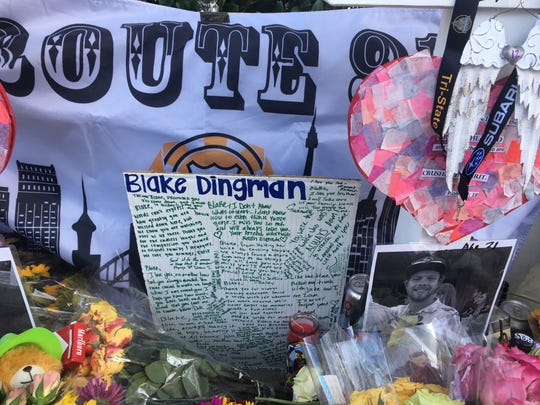 Flowers and messages pile up near a white cross for Blake Dingman, one of the 12 killed in the Borderline shooting. He was 21.