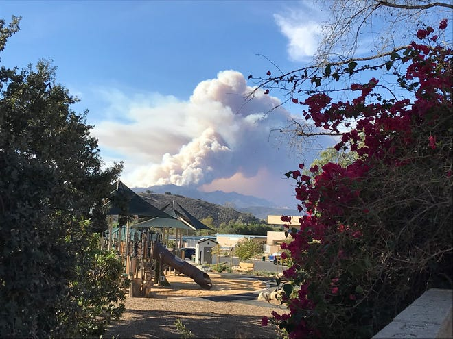 A large cloud of smoke hovers up from the Woolsey Fire.