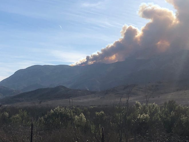 Smoke from a flare-up in the Lake Sherwood area billows up Tuesday morning as the Woolsey Fire continues to burn through the region.