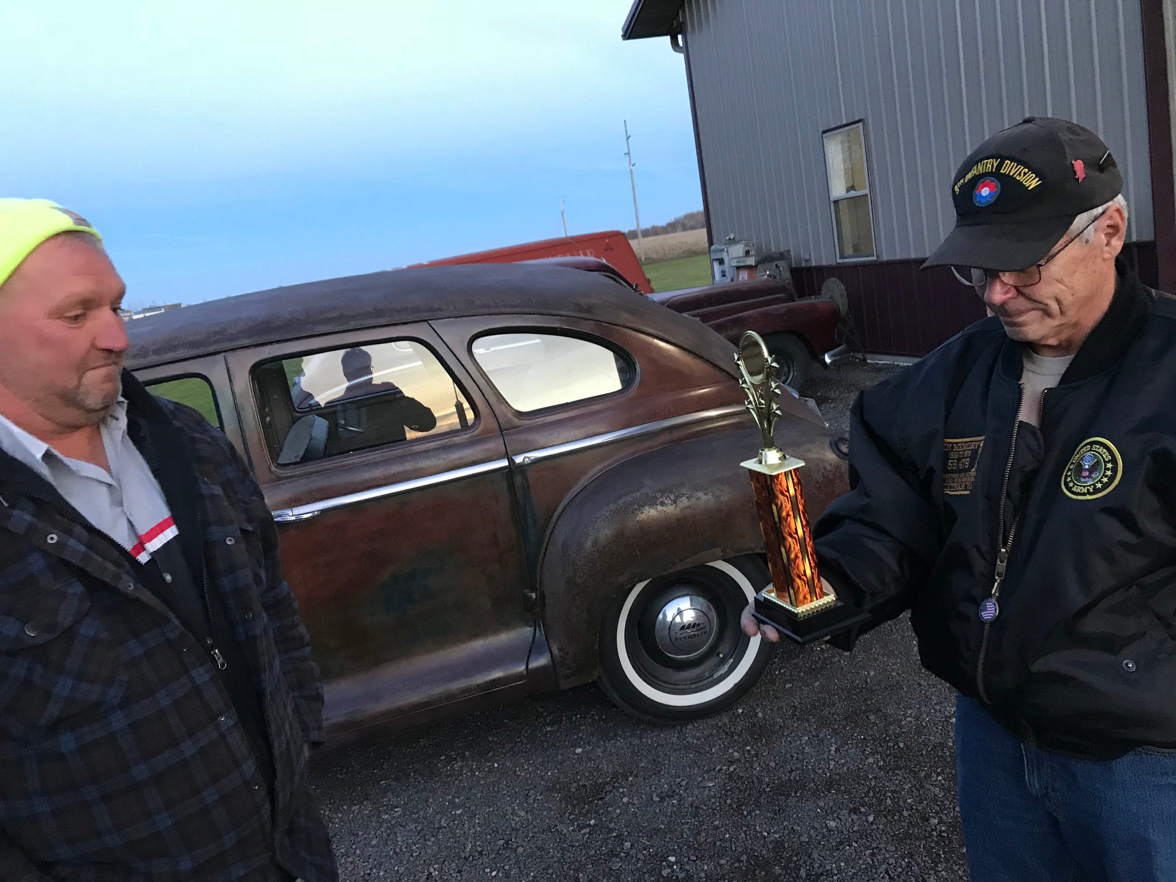 "Dale Lindwall (right) chokes up after Tim Dupee gives him a trophy the 1948 Plymouth won at a car show. ""You did this,"" Tim said, as he handed the award to Dale."