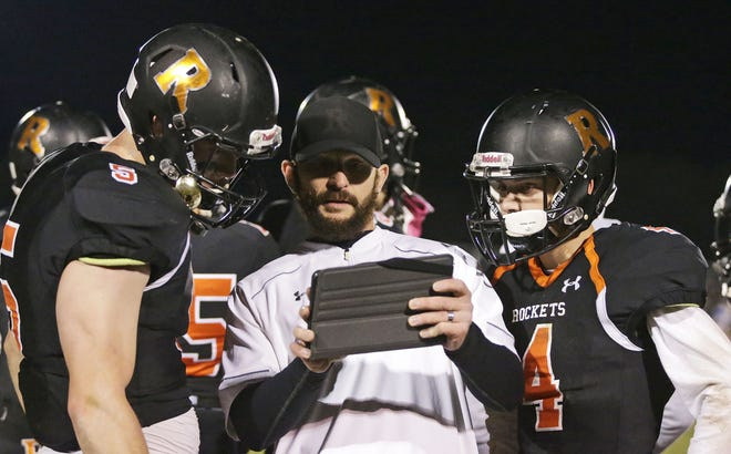 Cedar Grove-Belgium assistant coach/defensive coordinator Jason Klein, center, points out a plan on a tablet to Wade Navis, left, and Jeffrey Emperley, during a break in action in a game against Howards Grove in October.