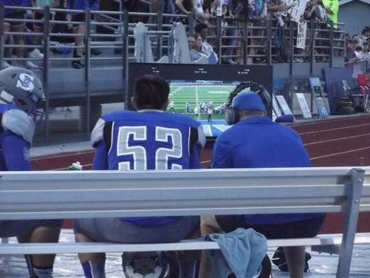 A Green Bay Southwest player and coach study a replay on a sideline montor in this photo from the 2016 high school football season.