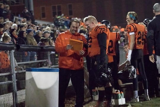 Marshfield offensive lineman Aric Folz, right, looks over a replay with a Tigers assistant coach on a table during a WIAA Division 2 second-round playoff game against Menasha at Beell Stadium.