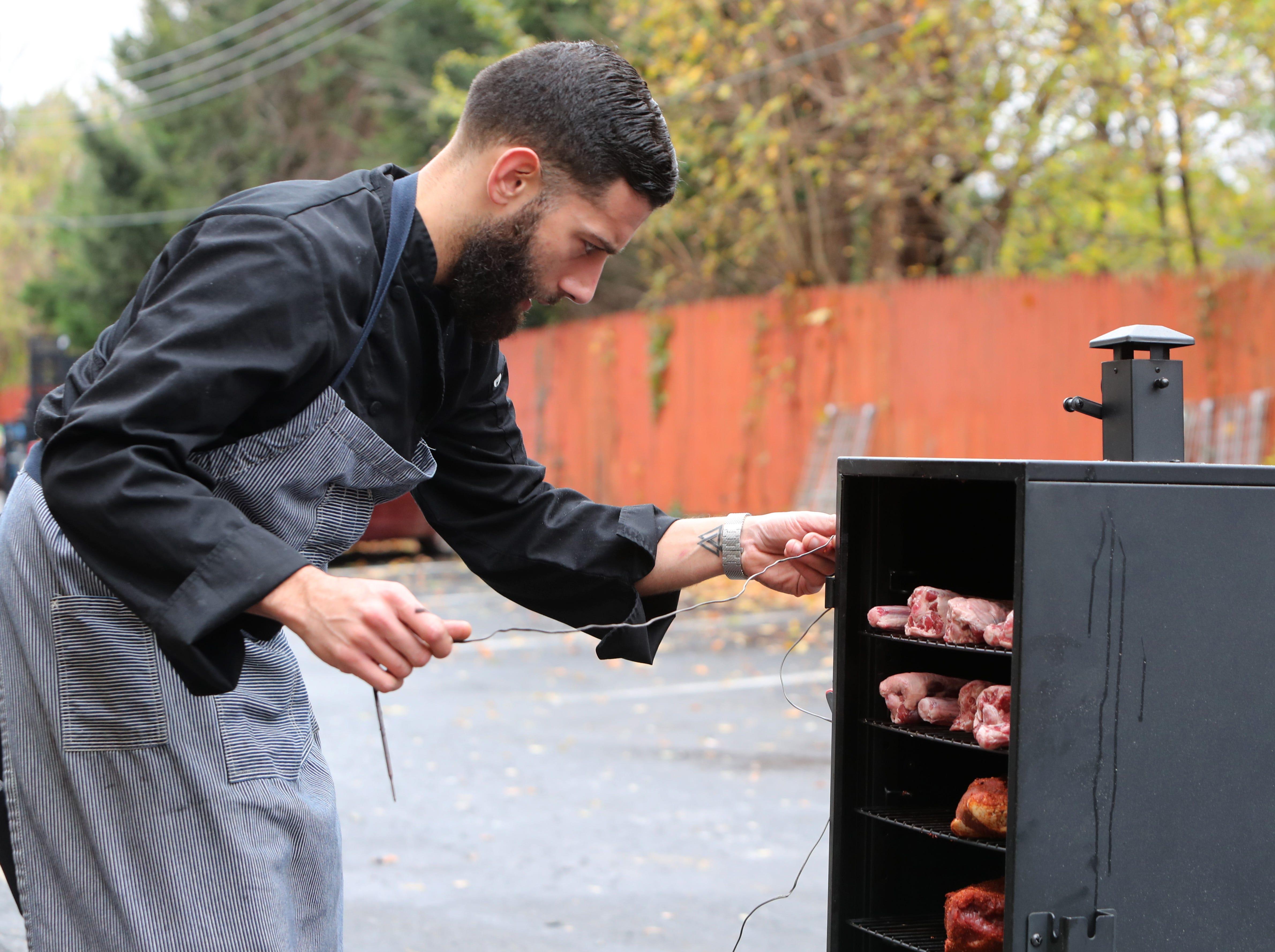 Chef Gustavo Gutierrez loads a smoker at the Ridge Steakhouse in Airmont Nov. 13, 2018.