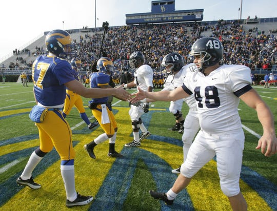 Delaware captains (from left) Pat Devlin, Matt Marcorelle and Tyrone Grant shake hands with their Georgia Southern counterparts after the coin toss to start their FCS playoff semifinal at Delaware Stadium in 2010.