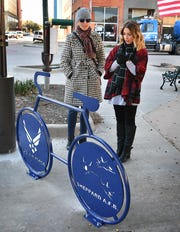 Becky Raeke, left, and Jana Schmader look over the newest special bike rack unveiled downtown at the corner of 8th Street and Indiana Ave. Tuesday afternoon.