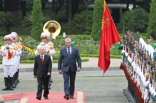 Vietnamese President Nguyen Phu Trong, left and his Cuban counterpart Miguel Diaz-Canel, right, review an honor guard in Hanoi, Vietnam. Diaz-Canel is on a three-day visit to Vietnam to boost ties between the two Communist allies and part of his first international tour since taking office in April.