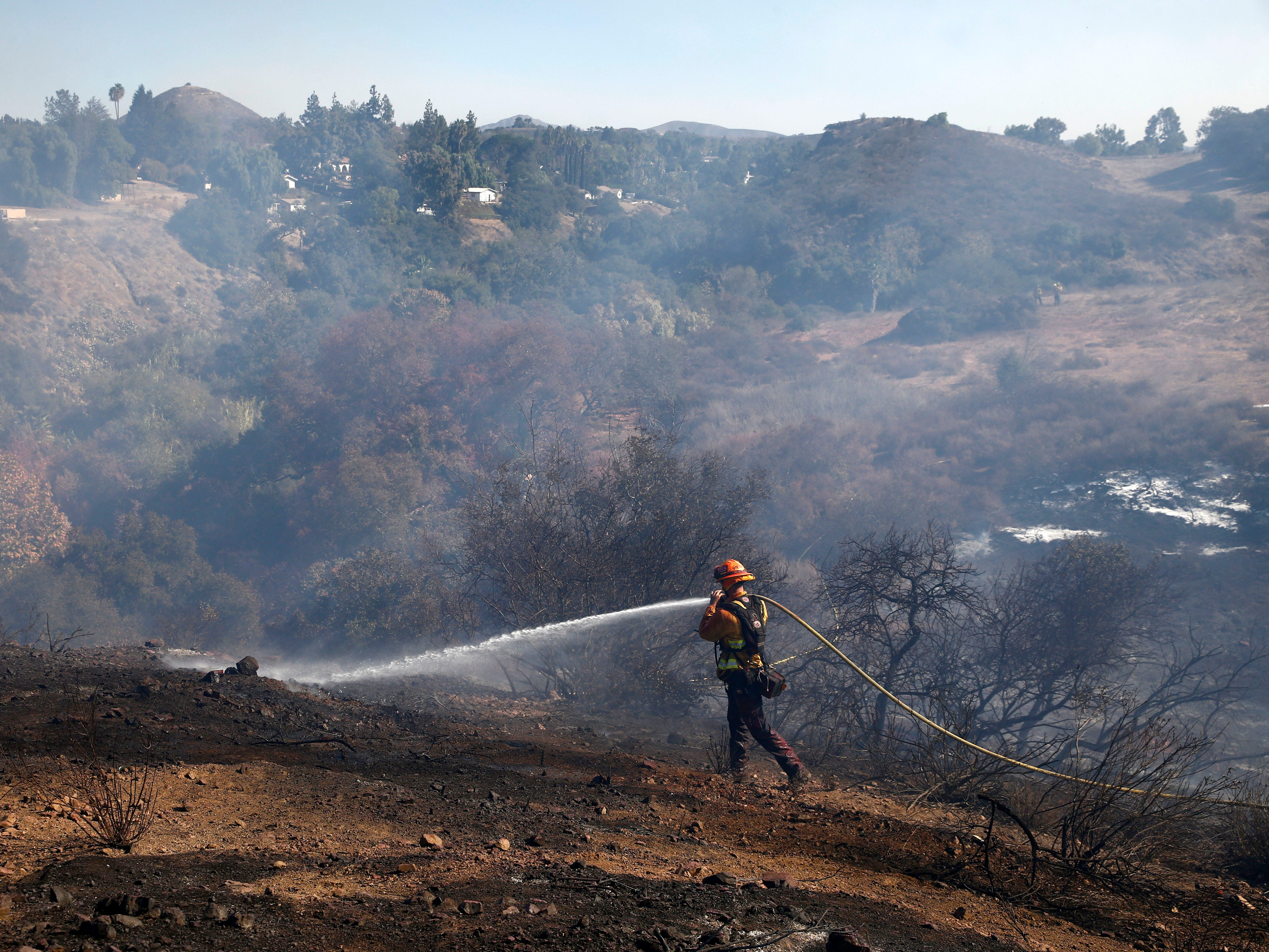 A firefighter puts out hotspots as the Hill Fire burns on Nov. 12, 2018, in Thousand Oaks, Calif.