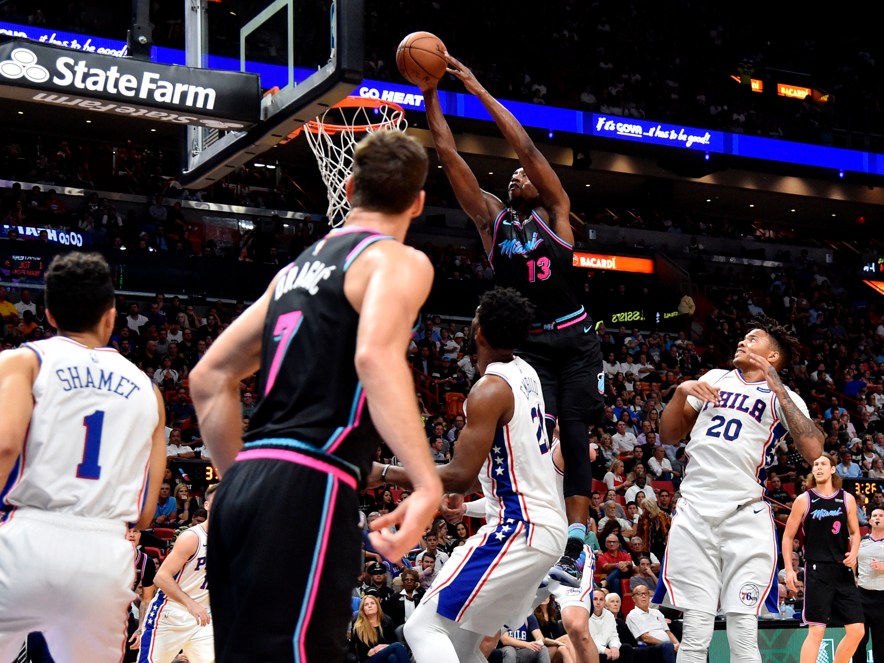 Nov. 12: Heat center Bam Adebayo (13) throws it down with two hands as 76ers defender Joel Embiid looks on during the second half in Miami.