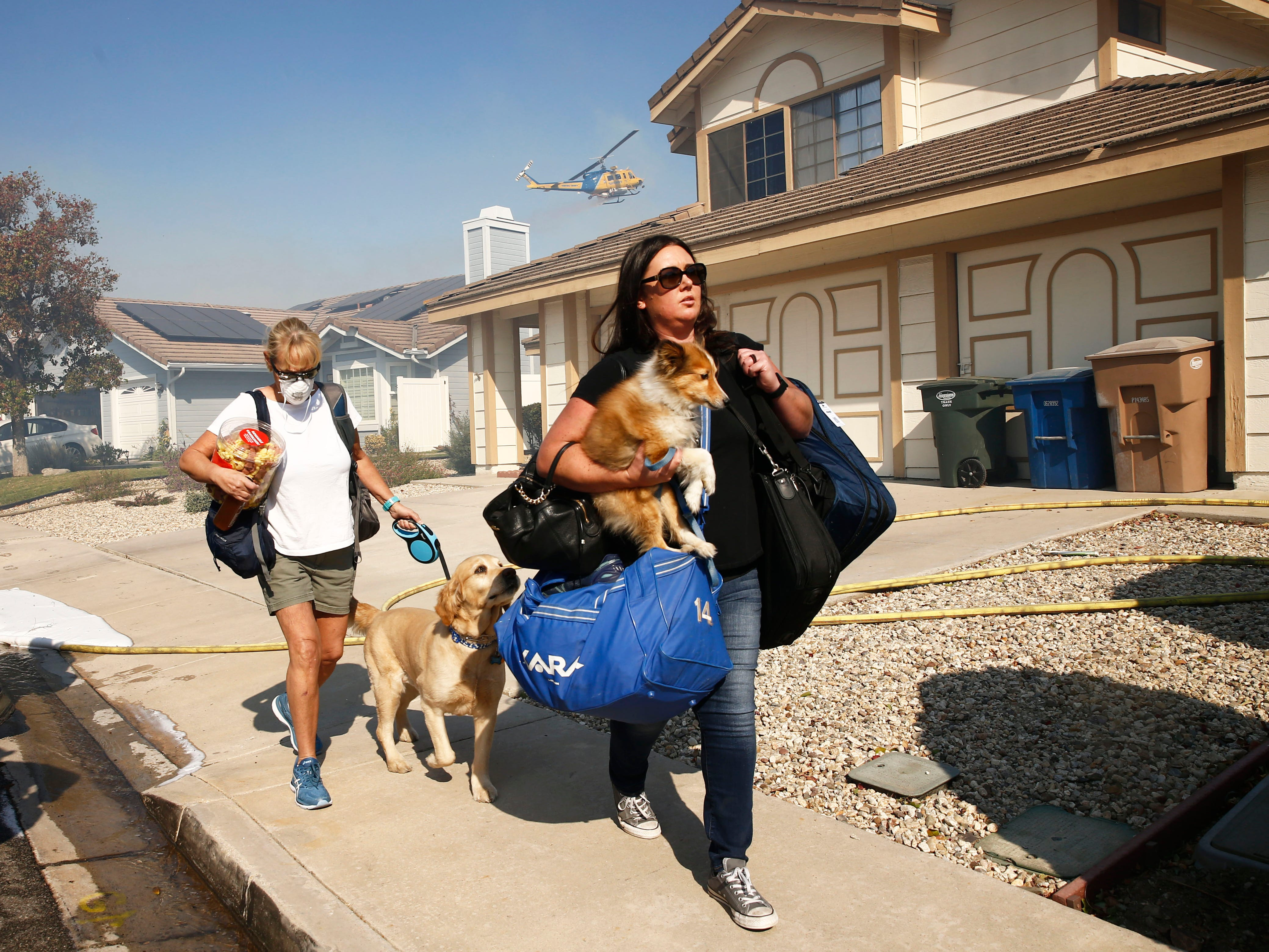 Residents evacuate with their pets as the Hill Fire burns on Nov. 12, 2018, in Thousand Oaks, Calif.