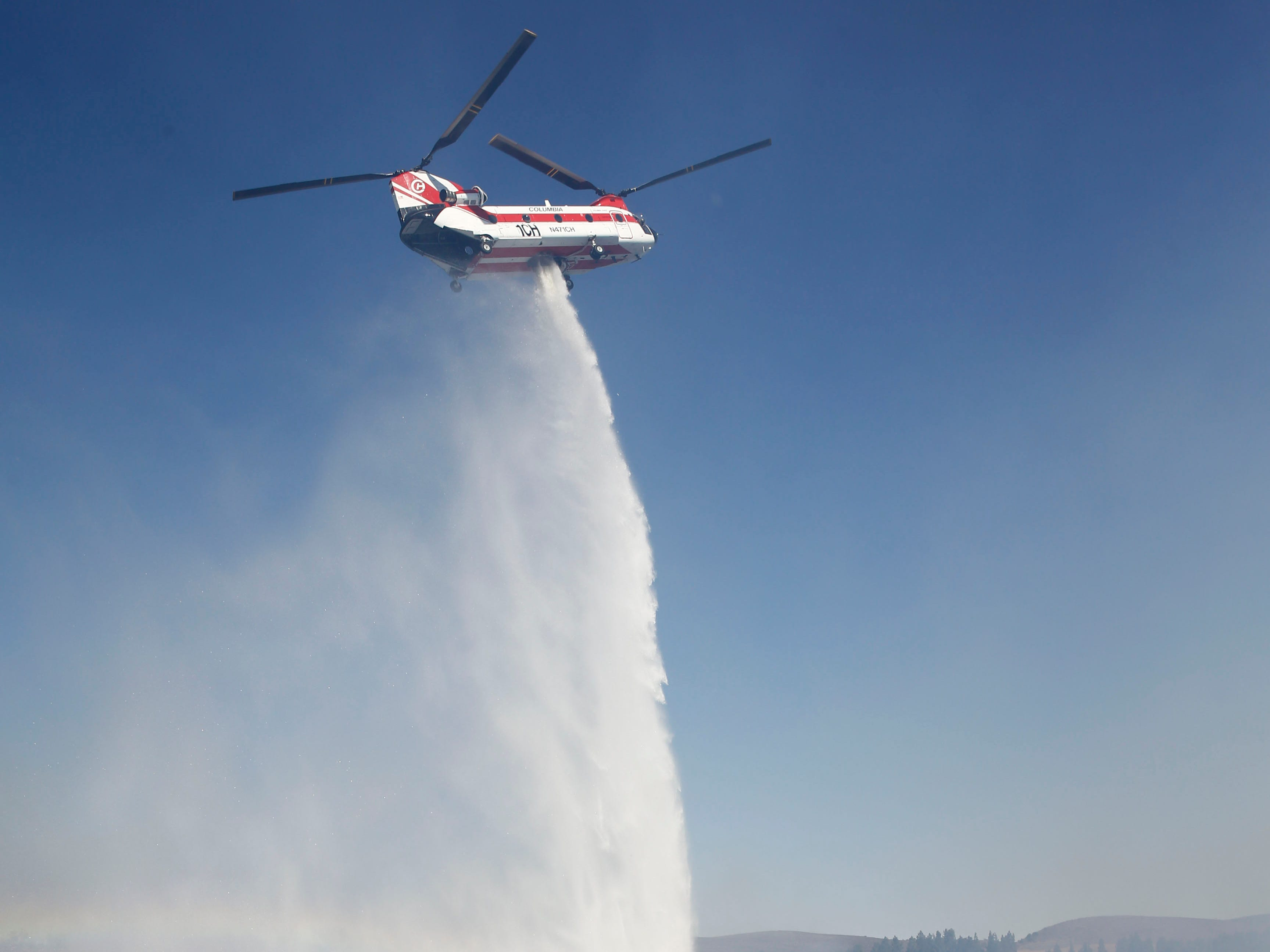 A helicopter drops water on the Hill Fire in Thousand Oaks, Calif. on Nov. 12, 2018.