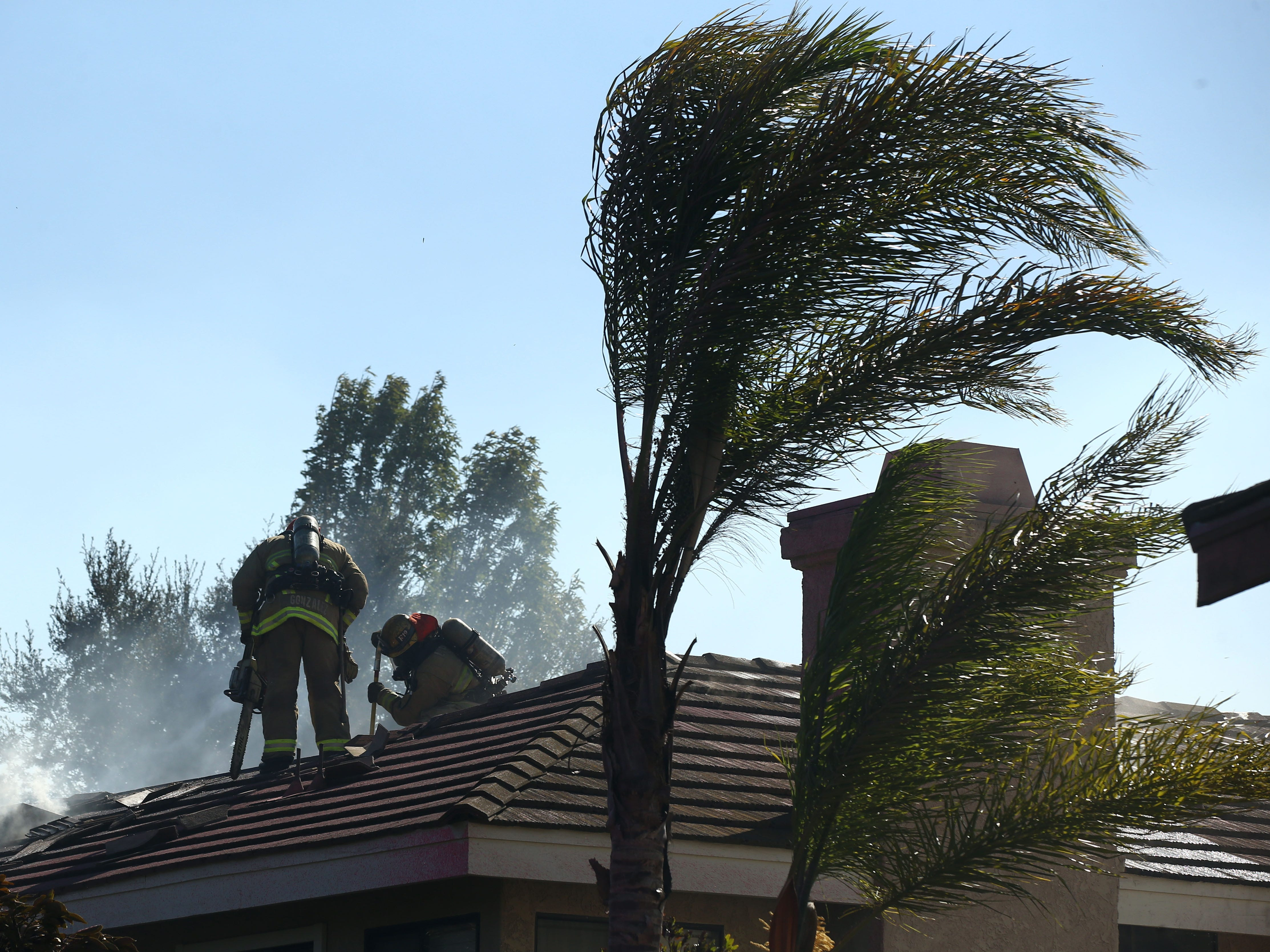 Firefighters put out a fire on a roof as the Hill Fire burns on Nov. 12, 2018, in Thousand Oaks, Calif.