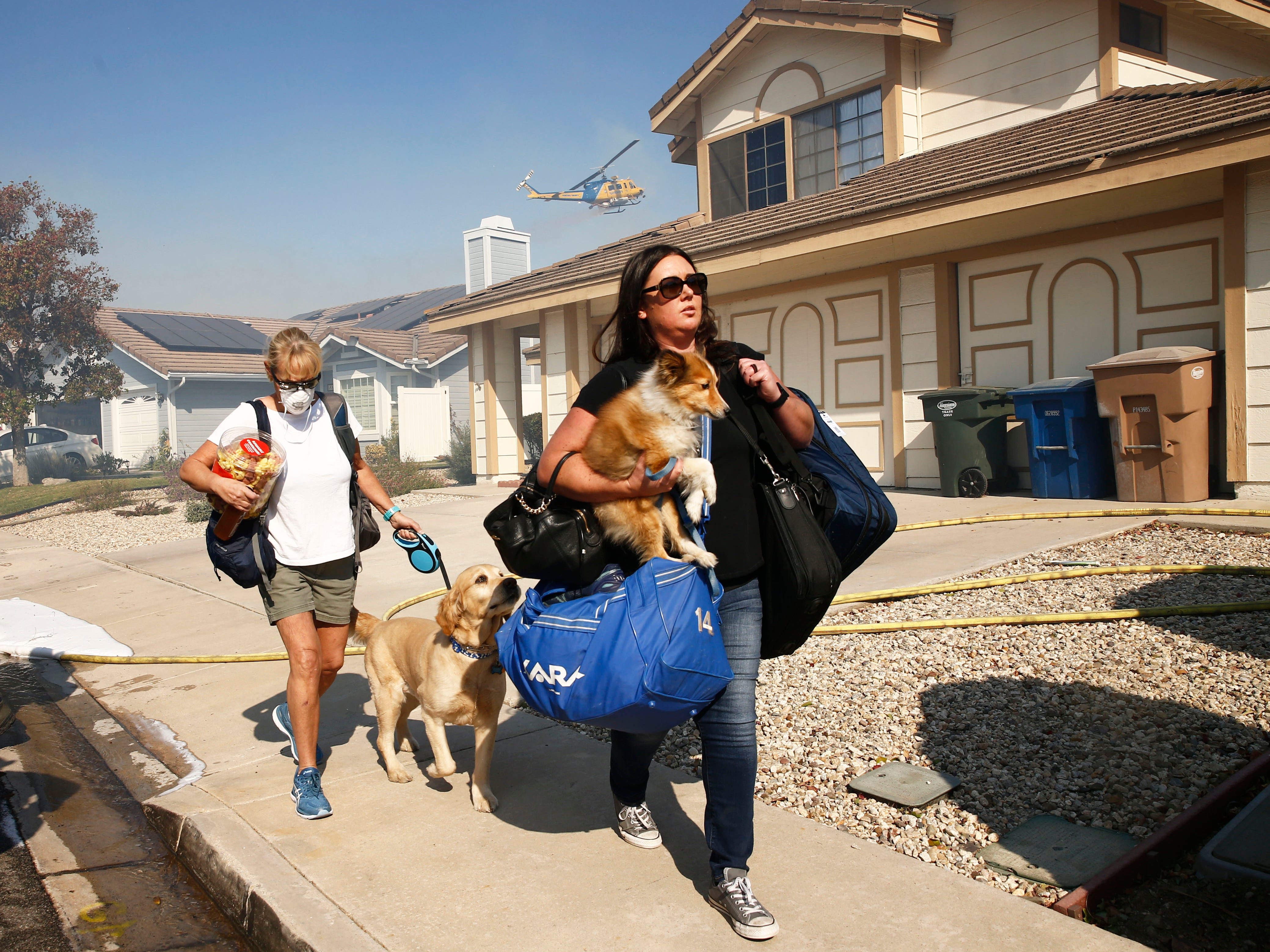 Residents evacuate with their pets as the Hill Fire burned in a canyon on Monday, Nov. 12, 2108, in Thousand Oaks, Calif.