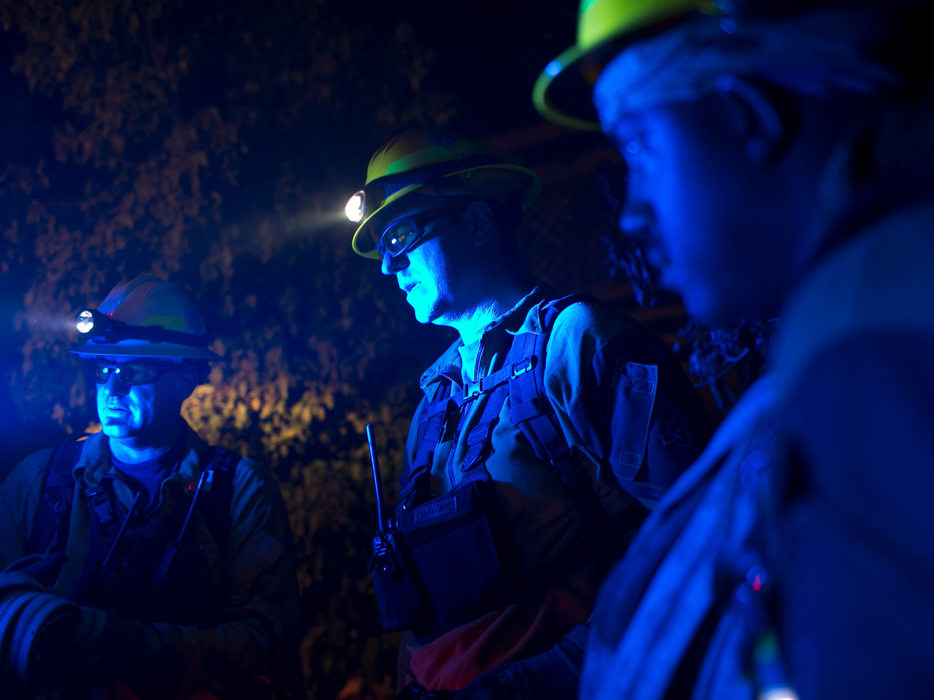 Firemen discuss their plan for an overnight shift protecting homes and property from the Camp Fire on Nov. 12, 2018, in Butte Valley, Calif.