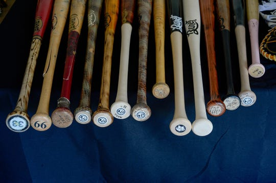 Custom bats from Baret Bats on top of a table in Juan Baret's Woodbridge, Virginia, home. Baret, 39, is a disabled Air Force veteran who founded a baseball bat making business in 2013 after his injuries took him out of the game.