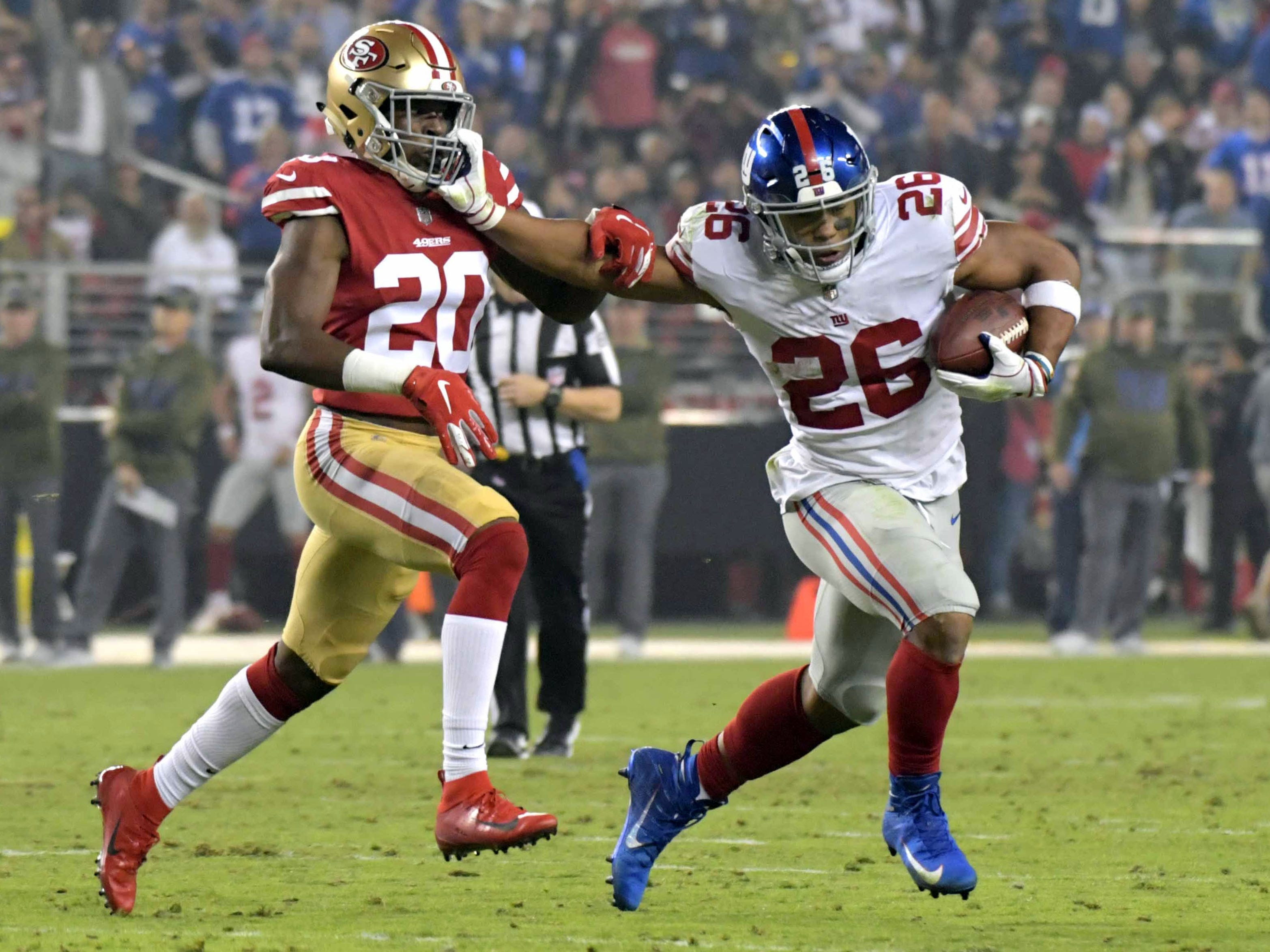 New York Giants running back Saquon Barkley is defended by San Francisco 49ers cornerback Jimmie Ward in the second quarterat Levi's Stadium.