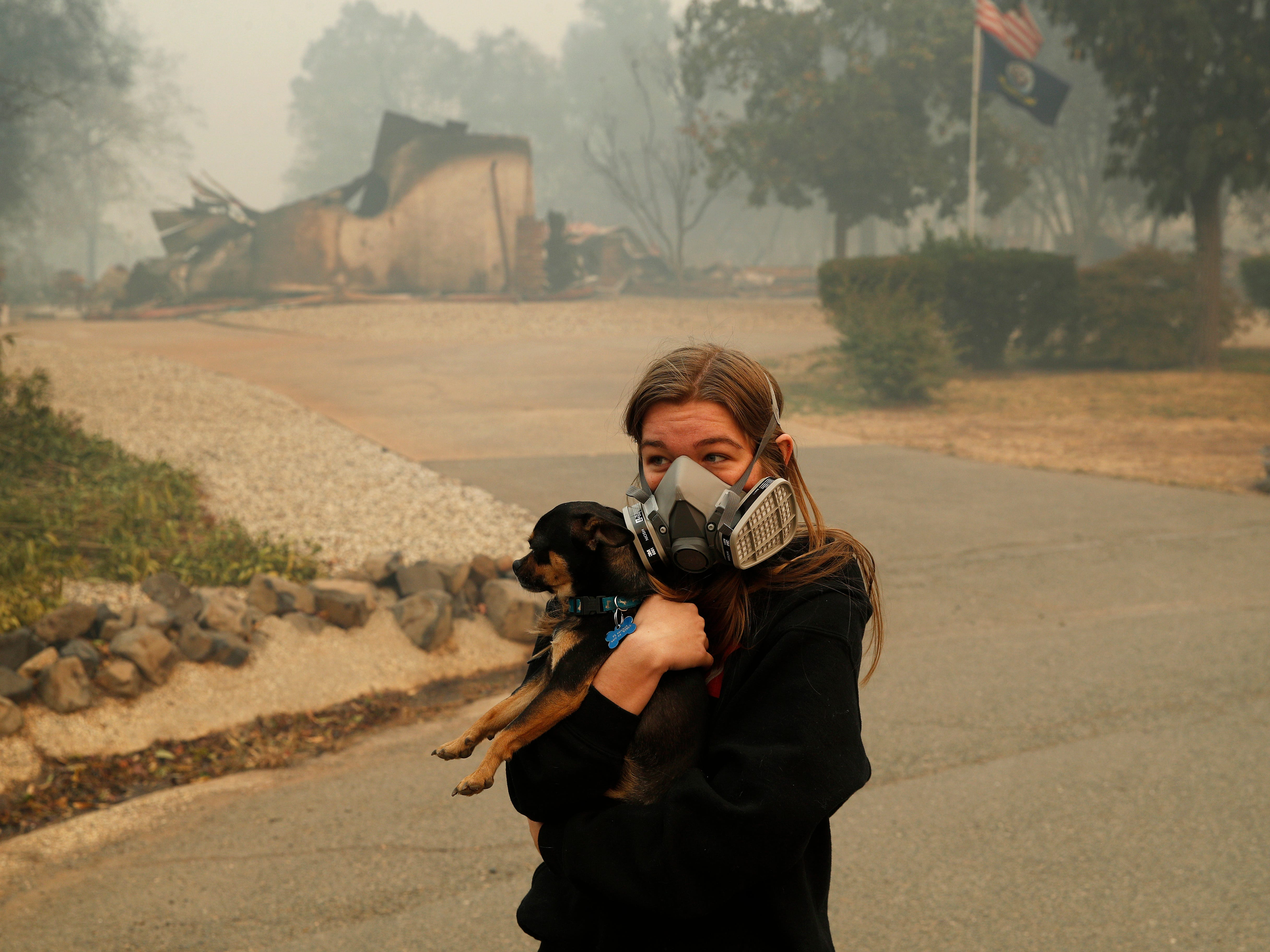 Araya Cipollini, 19,  holds on to her dog T.J. near the burned out remnants of her neighbor's home burned in the Camp Fire, Saturday, Nov. 10, 2018, in Paradise, Calif. Cipollini and her family lost their home nearby in the fire.