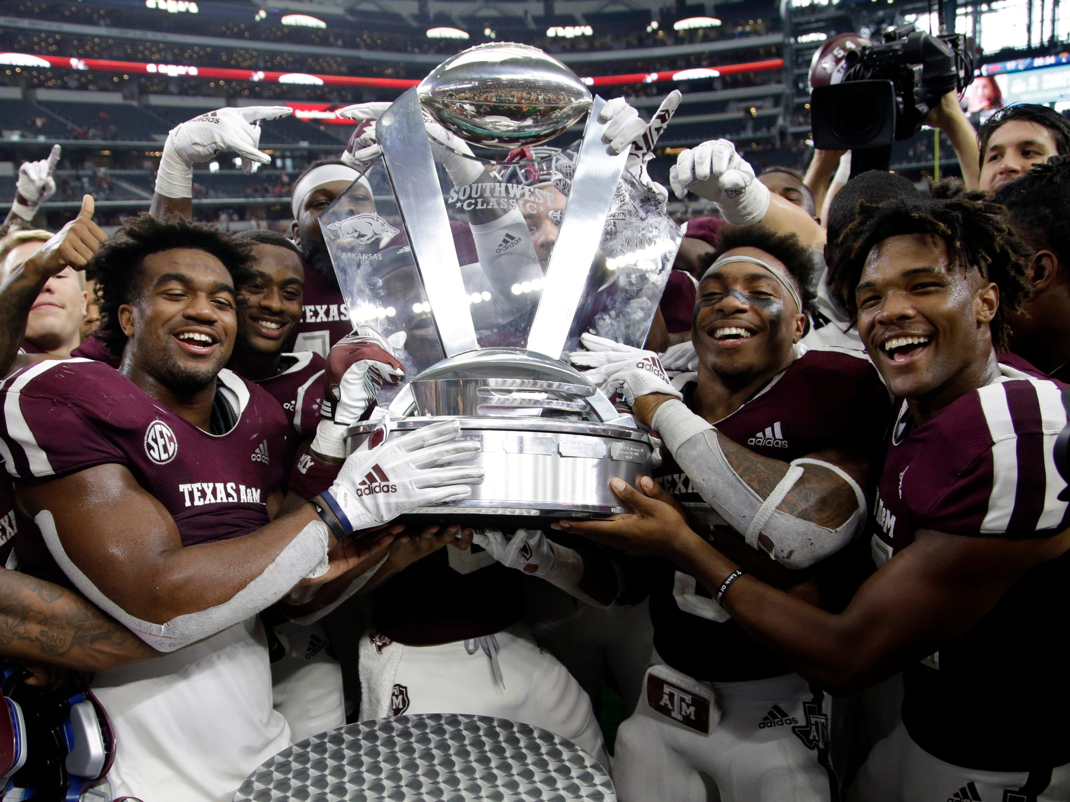 Southwest Classic Trophy: Texas A&M players hold up the Southwestern Classic Trophy after a 24-17 win over Arkansas at AT&T Stadium on Sept. 29.