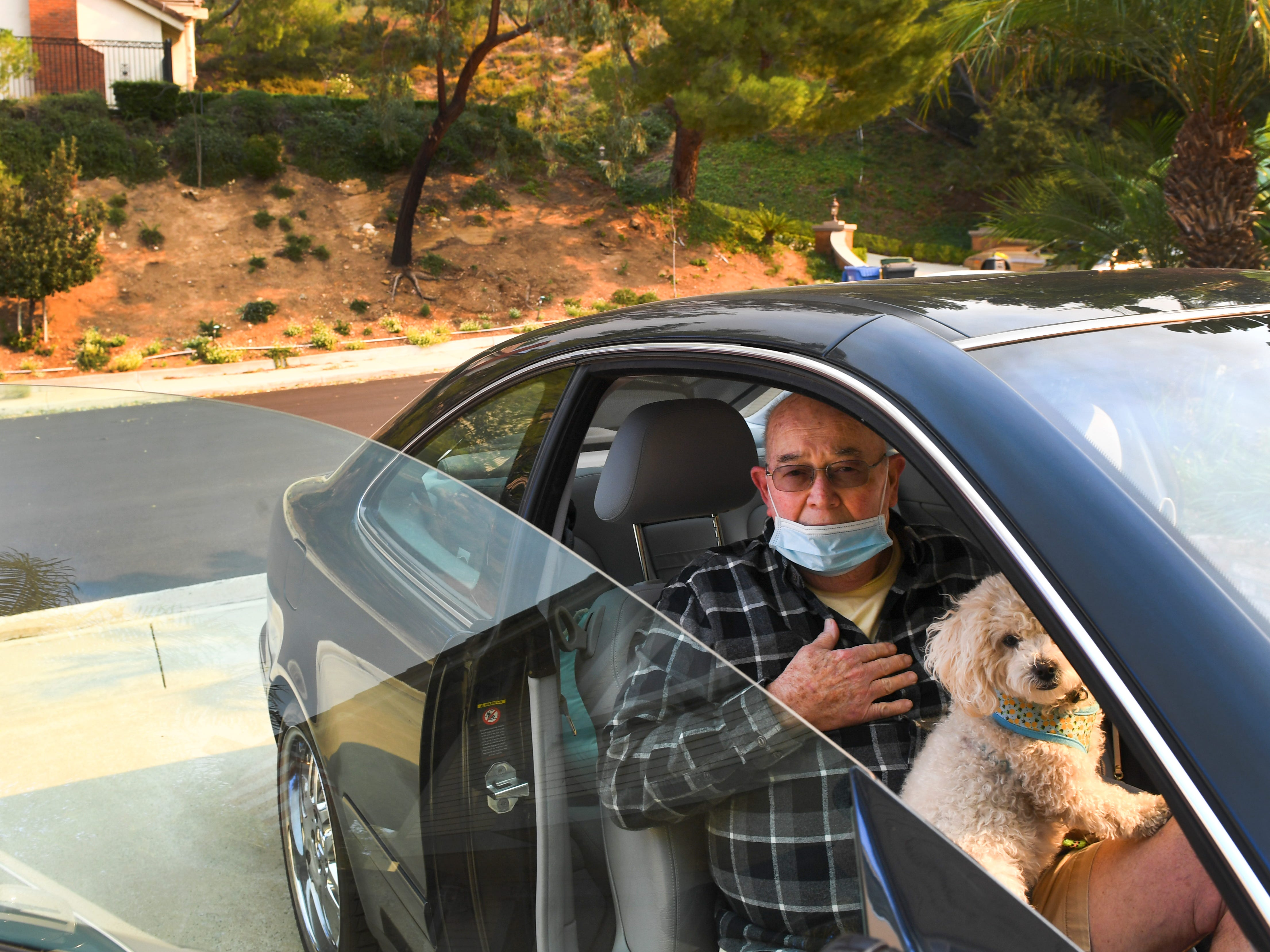Jeff Riley waits to be evacuated from his home with the family dog, Nov. 9, 2018, in Thousand Oaks, Calif.