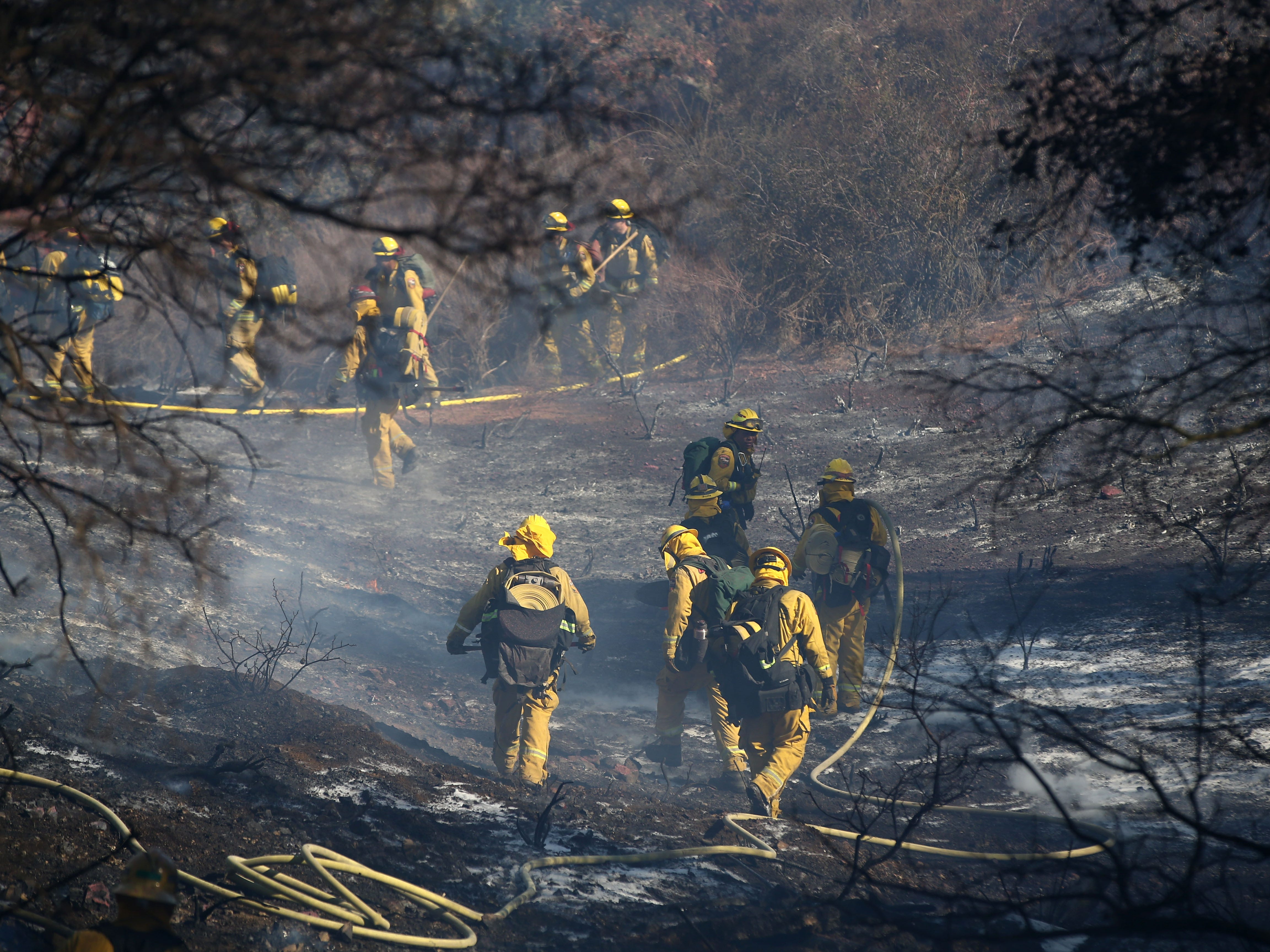 Firefighters put out a hotspot as the Hill Fire burns on Nov. 12, 2018, in Thousand Oaks, Calif. Ventura County firefighters saved all the homes in the area.