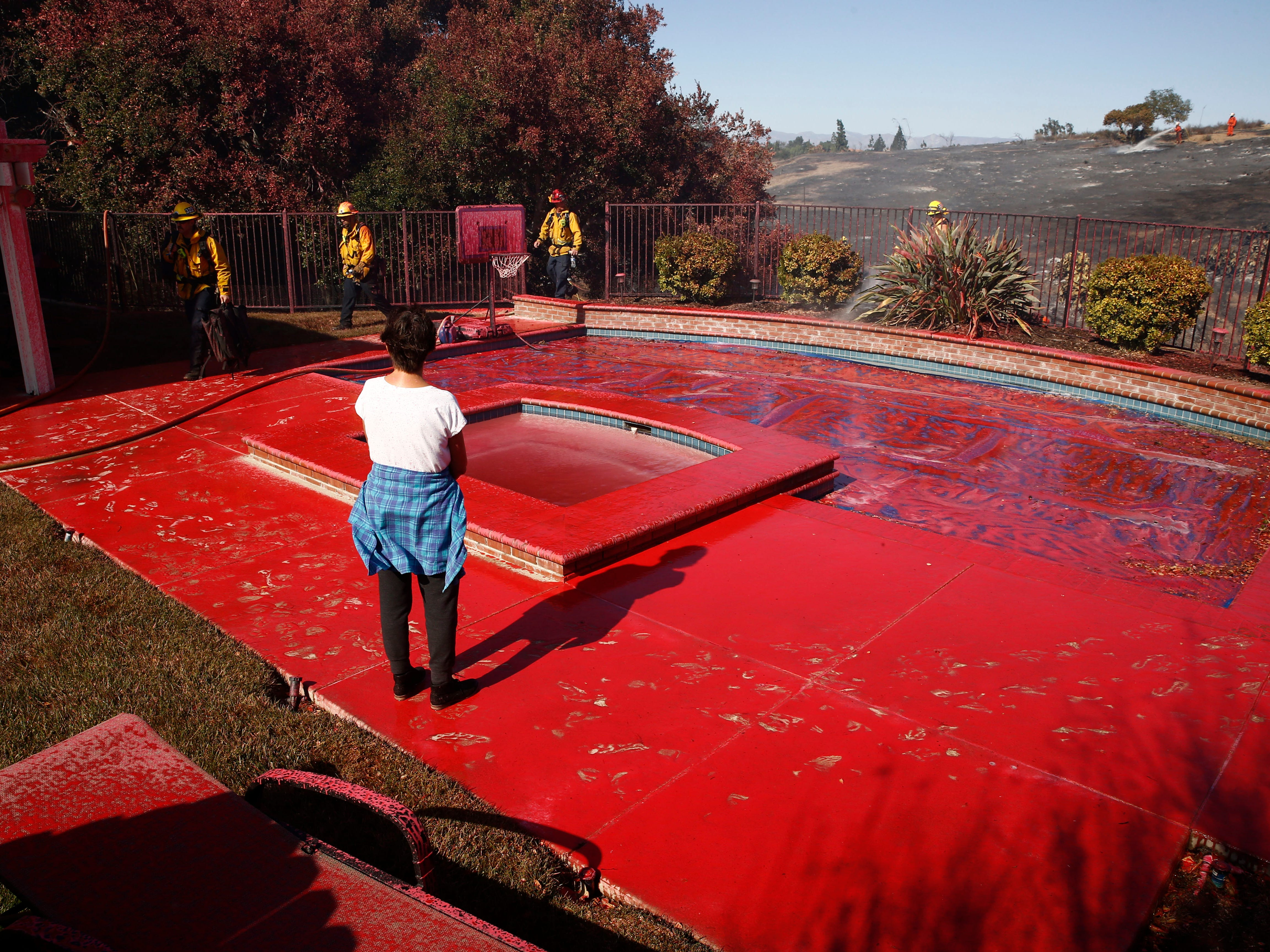 Linda Stamper's backyard is covered in fire retardant as the Hill Fire burns on Nov. 12, 2018, in Thousand Oaks, Calif. Ventura County firefighters saved all the homes in the area.