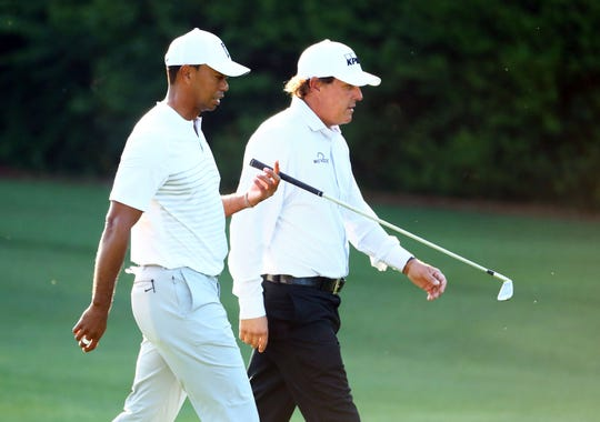 Tiger Woods and Phil Mickelson walk down the 11th fairway during a practice round for the Masters at Augusta National on April 3.
