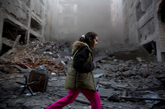 A Palestinian girl walks next to a destroyed residential building hit by Israeli airstrikes in Gaza City, on Nov. 13, 2018.