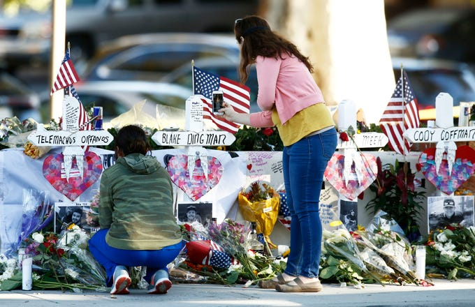 Visitors bring flowers and leave personal messages at the mass shooting memorial as the FBI and Ventura County Sheriff's office continue their investigation at the Borderline Bar and Grill on  Nov. 12, 2018, in Thousand Oaks, Calif.