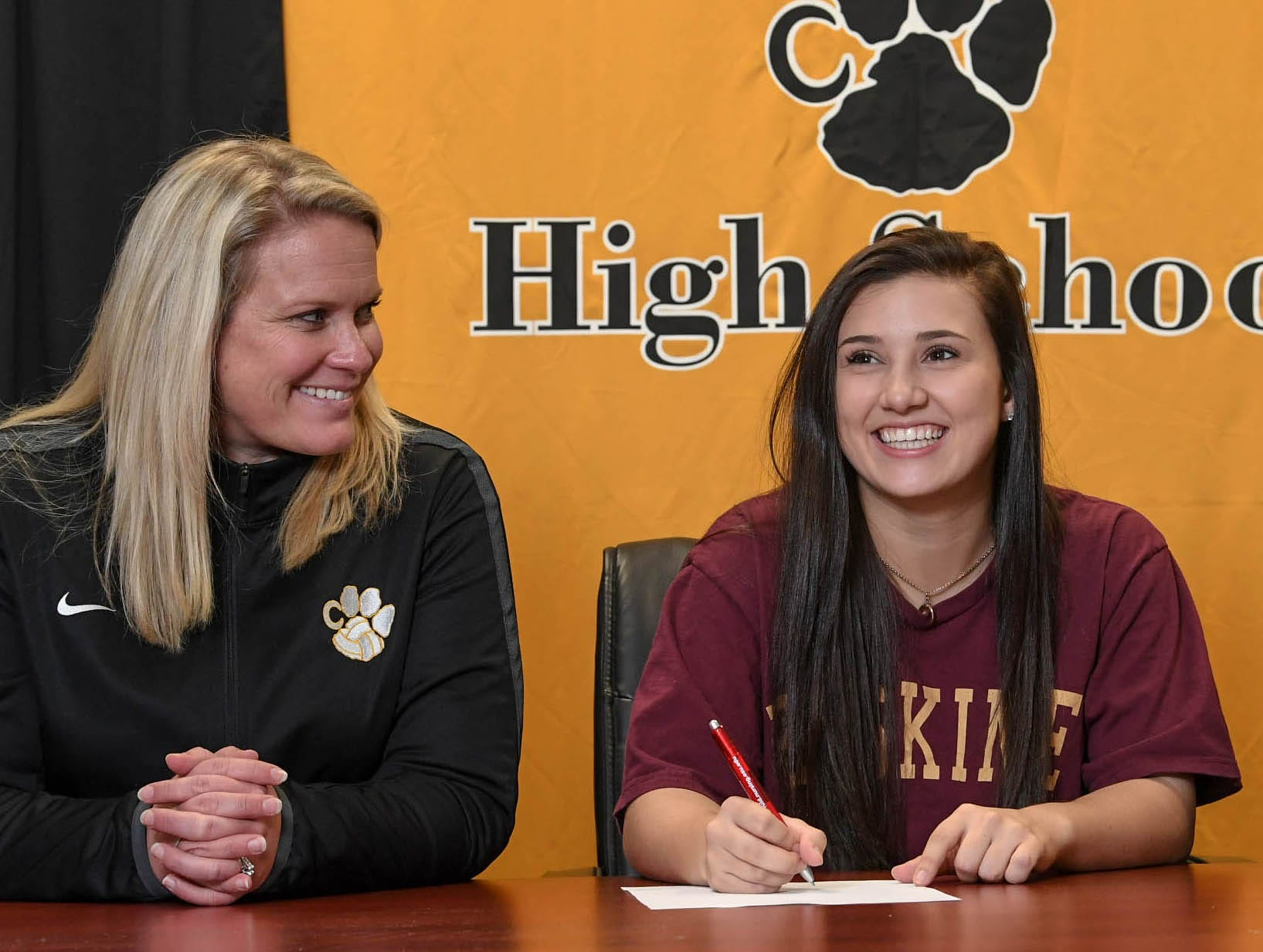 Lucy Bryant, right, signs a National Letter of Intent to play beach volleyball at Erskine College, near her high school volleyball coach Kristen Fouts, left, during a National Signing Day event at Crescent High School in Iva on Wedesday.
