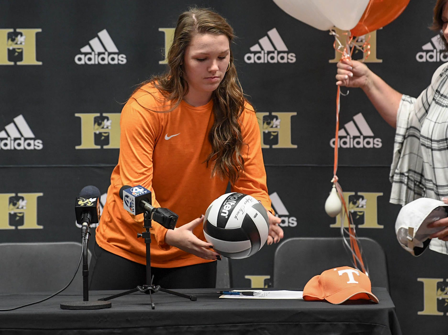 Maddie Bryant places a volleyball and Tennessee as props during a National Signing Day event at T.L. Hanna High School in Anderson on Wednesday. Bryant, All-Region Class AAAAA volleyball player for the Yellow Jackets signed with Tennessee.