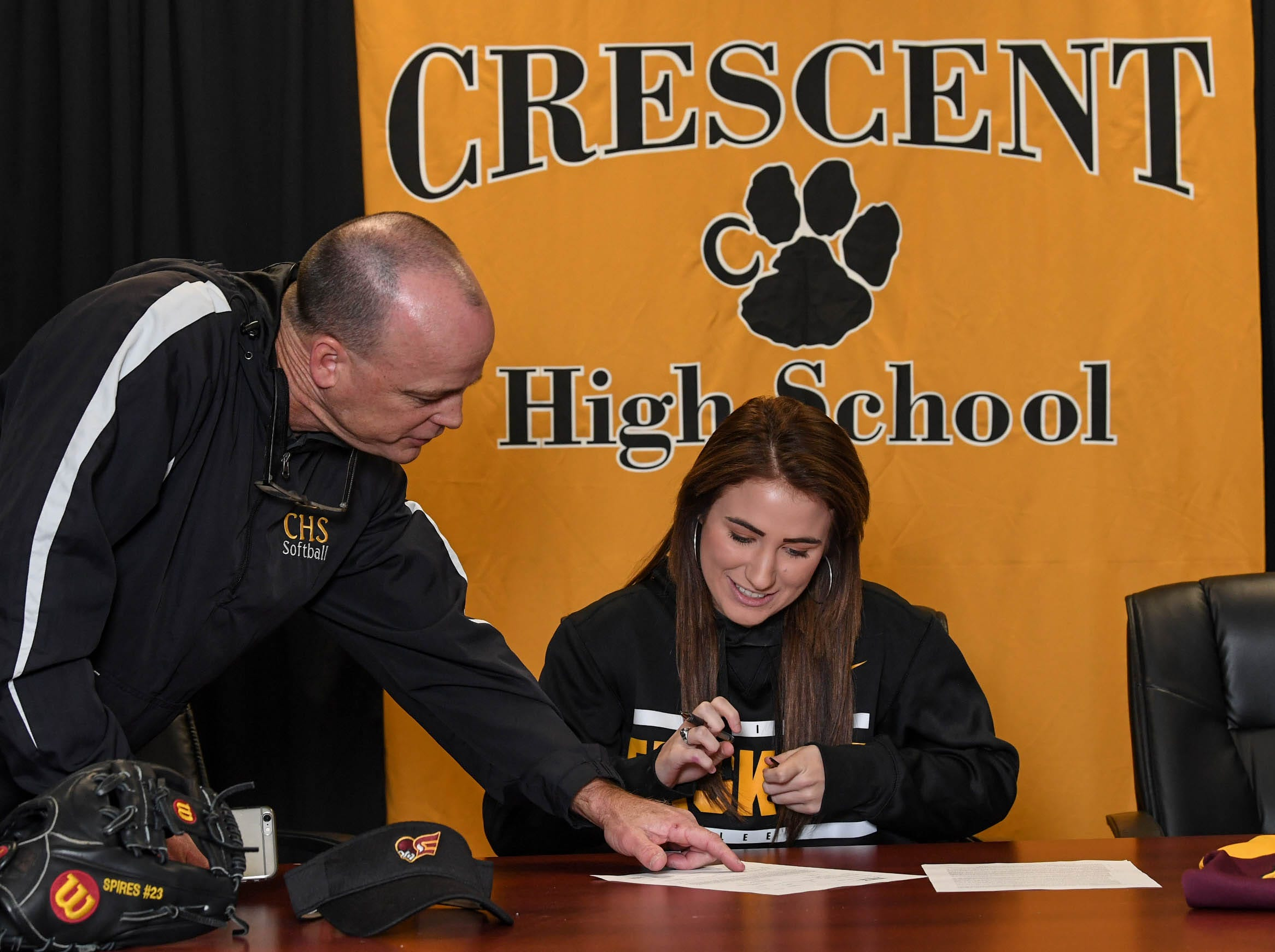 Jeff Craft, left, Crescent High School Athletic Director, looks at a National Letter of Intent form with Katie Spires, signing to play softball at Erskine College, during a National Signing Day event at Crescent High School in Iva on Wedesday.