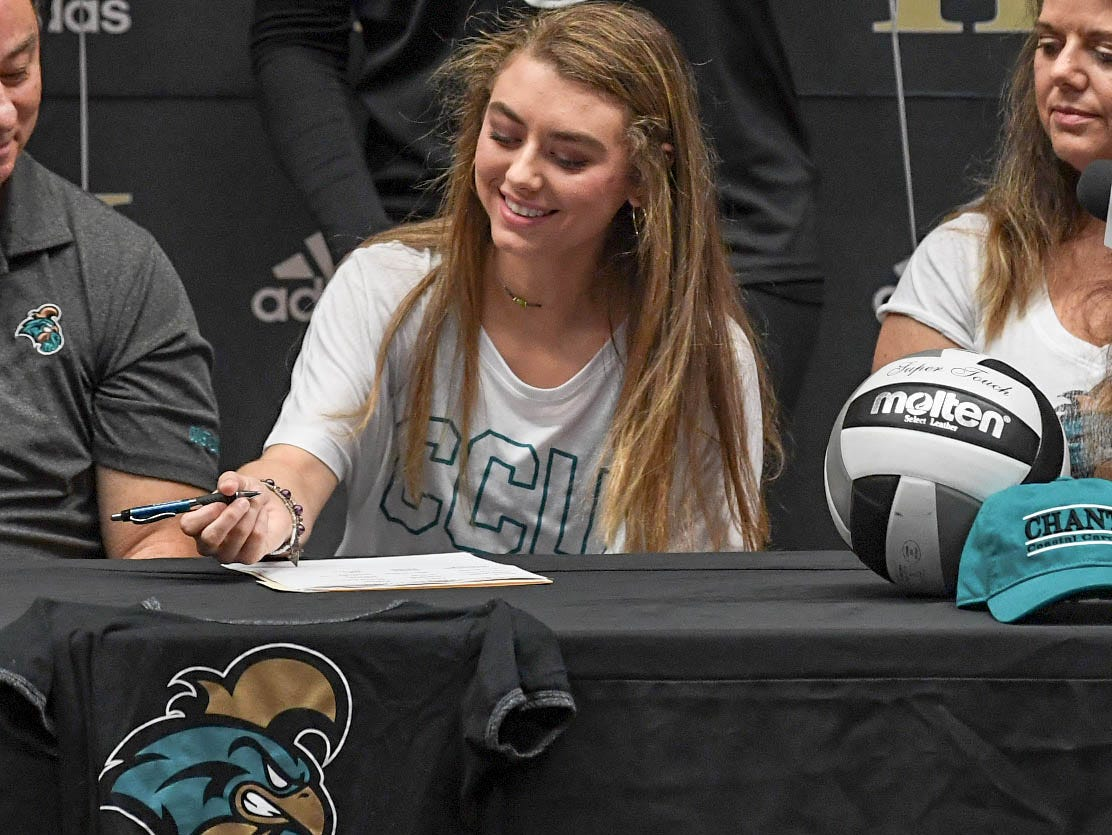 Zarah Fowler signs a letter of intent to play volleyball at the Coastal Carolina University, during a National Signing Day event at T.L. Hanna High School in Anderson on Wednesday.