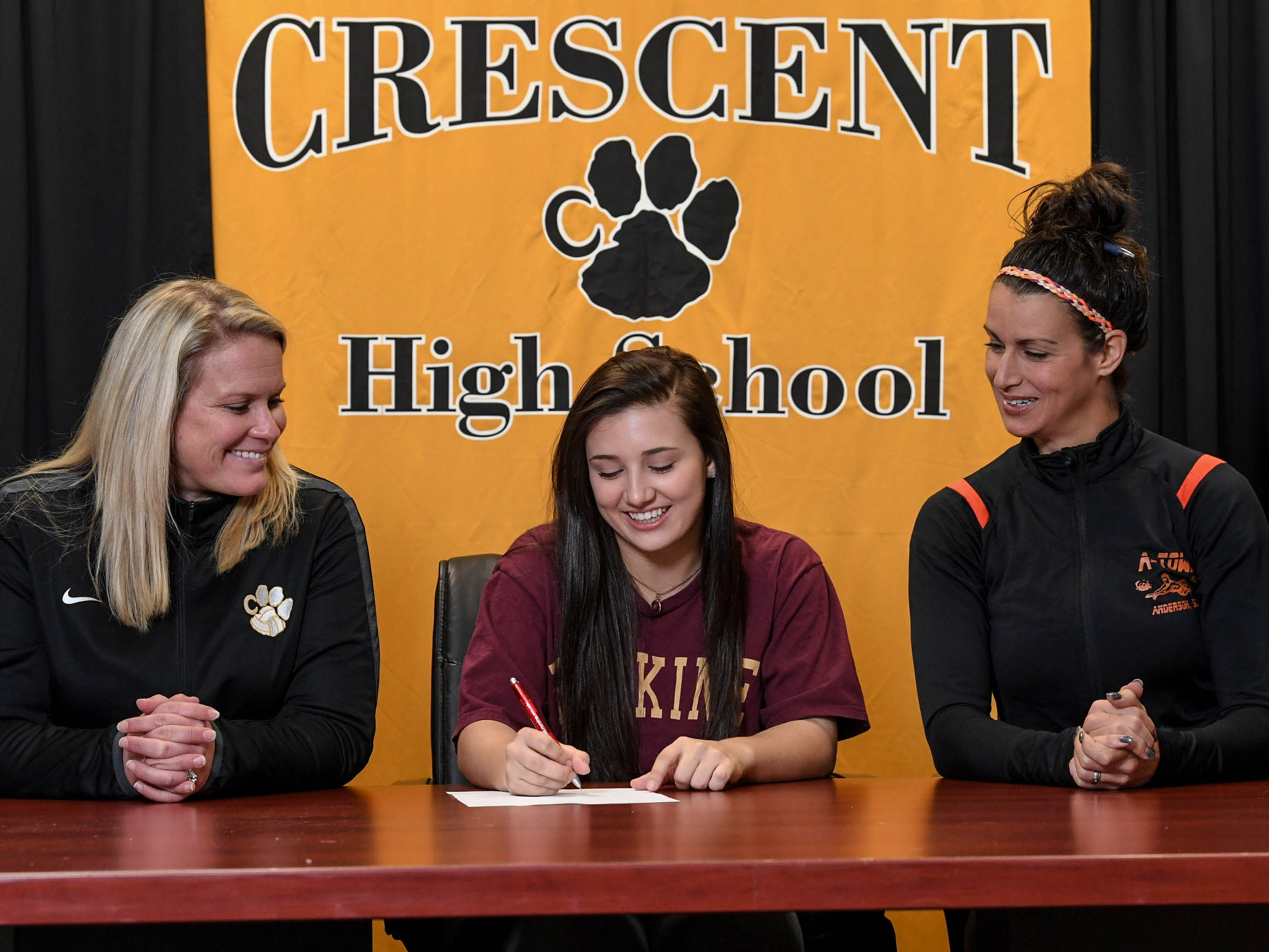 Lucy Bryant, middle, signs a National Letter of Intent to play beach volleyball at Erskine College, near her high school volleyball coach Kristen Fouts, left, and club volleyball coach Angel Freeze, right, during a National Signing Day event at Crescent High School in Iva on Wedesday.