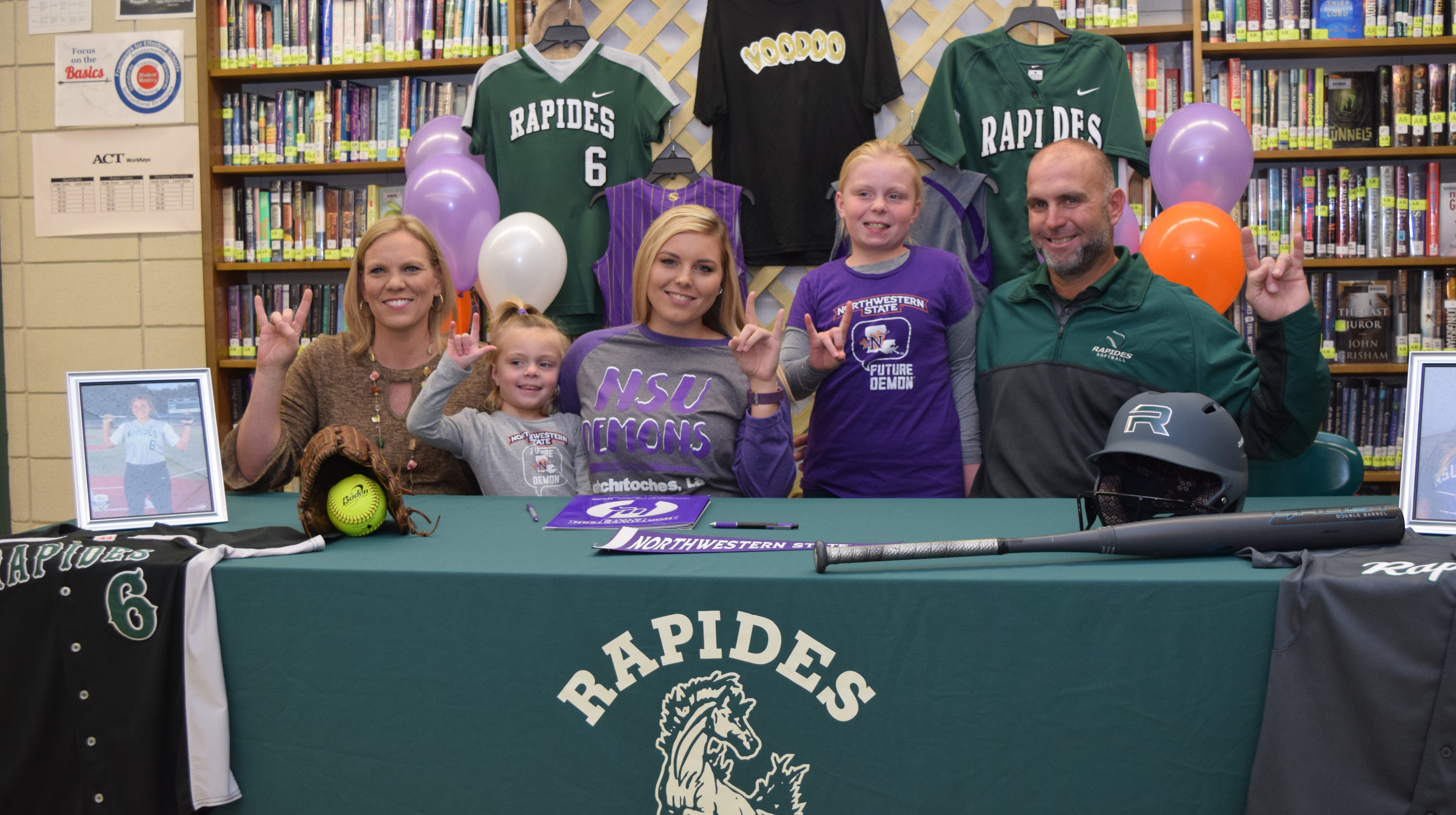 """Rapides High School's Sydney Lewis (third from left) and her family: mom Amy Lewis (far left); sisters Annabelle Lewis (second from left) and Ryan Lewis (second from right) and dad Heath Lewis show """"Fork 'Em Demon"""" hand signs after Sydney signed papers to play softball for Northwestern State University."""