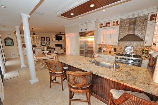 The kitchen features an expansive center island with a double sink and granite stone.