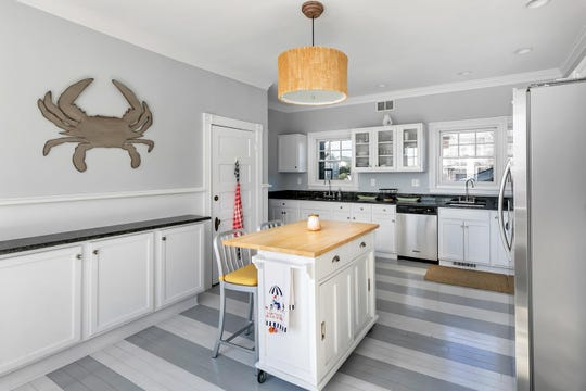 The kitchen features amazing painted wood floors with granite counter tops.