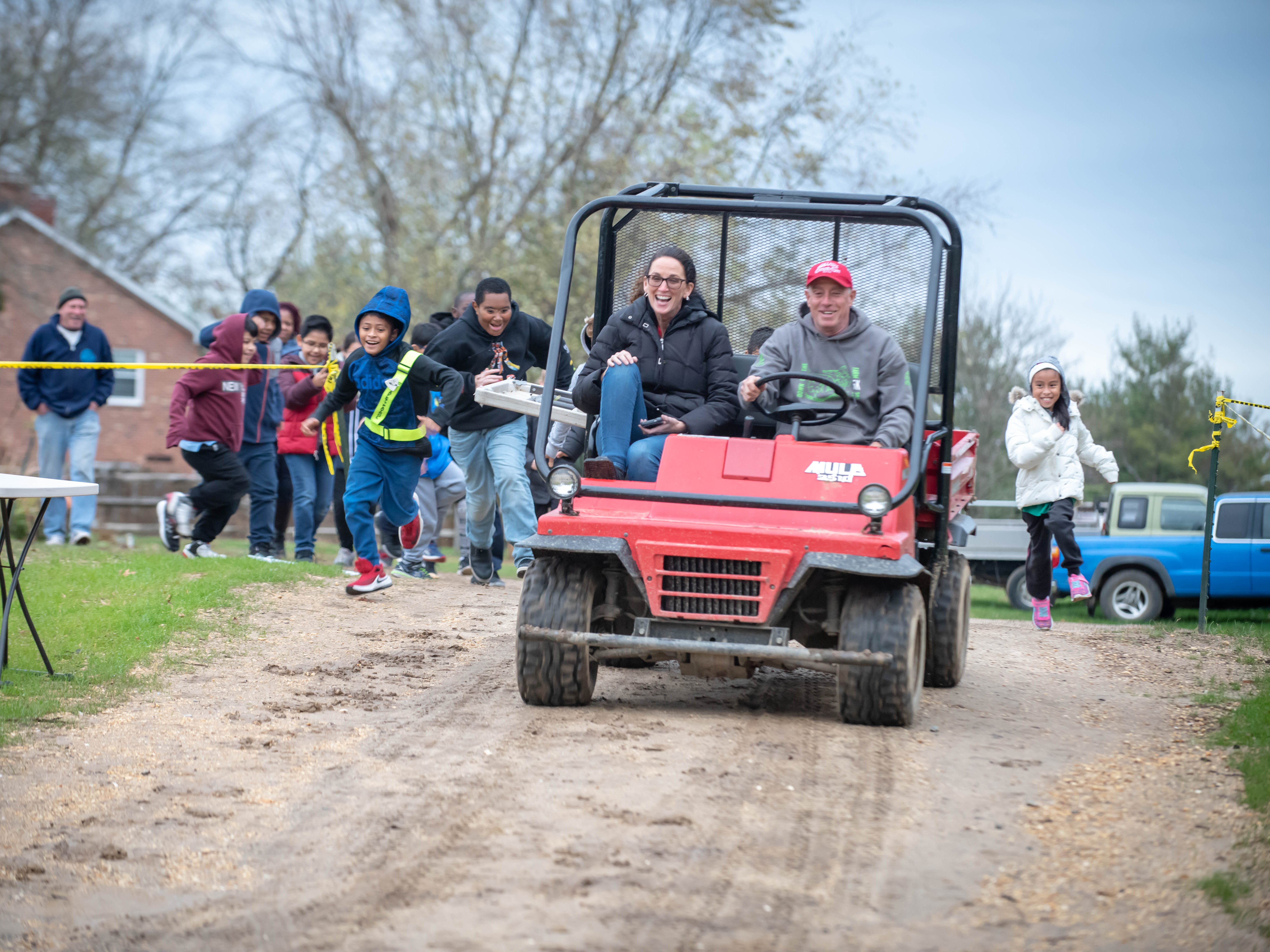 11/13/18- Sean Burney (center) co-founder of Allaire Community Farm, Wall Twsp.,( driving) as students from Woodrow Wilson school in Neptune City and 21st Century after school program , Bradley elementary school in Asbury Park race him down a hill. Seated with Burney is 4th grade teacher from Woodrow Wilson  Karen Bonney  photo/James J. Connolly/Correspondent