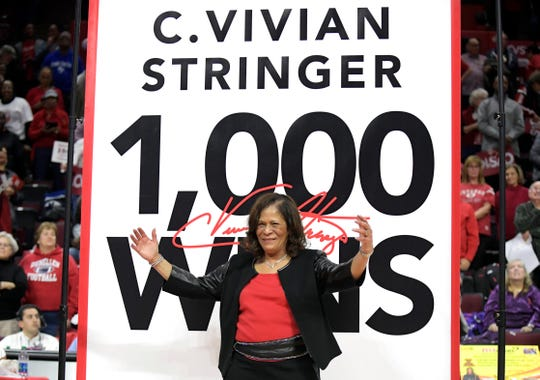 Rutgers head coach C. Vivian Stringer poses in front of a banner that will hang from the rafters after Rutgers defeated Central Connecticut for Stringer's 1,000th career NCAA college basketball game win, Tuesday, Nov. 13, 2018, in Piscataway, N.J. (AP Photo/Bill Kostroun)
