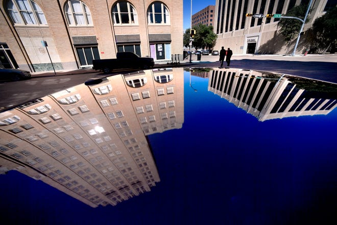 Pedestrians walk up to the Hotel Wooten Nov. 14.  The hotel, which was restored for apartments, and the West Texas Utilities Office Building are reflected in the roof of a parked car on North Third Street. Both structures were designed by Abilene architect David Castle.