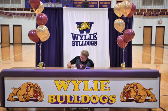 Wylie catcher Caleb Munton signs a Letter of Intent to play baseball at Texas State during a ceremony at Bulldog Gym on Nov. 14, 2018.
