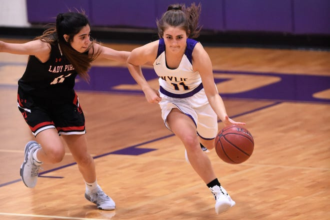 Wylie guard Madi Latham (11) goes past a Lubbock Cooper defender during a nondistrict game on Tuesday, Nov. 13, 2018, at Bulldog Gym. The Lady Bulldogs won 51-47.