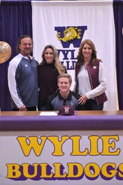 Wylie's Caleb Munton, middle, poses with father, Dan; sister, Kassidy; and mother, Tracy, during a ceremony at Bulldog Gym on Wednesday.