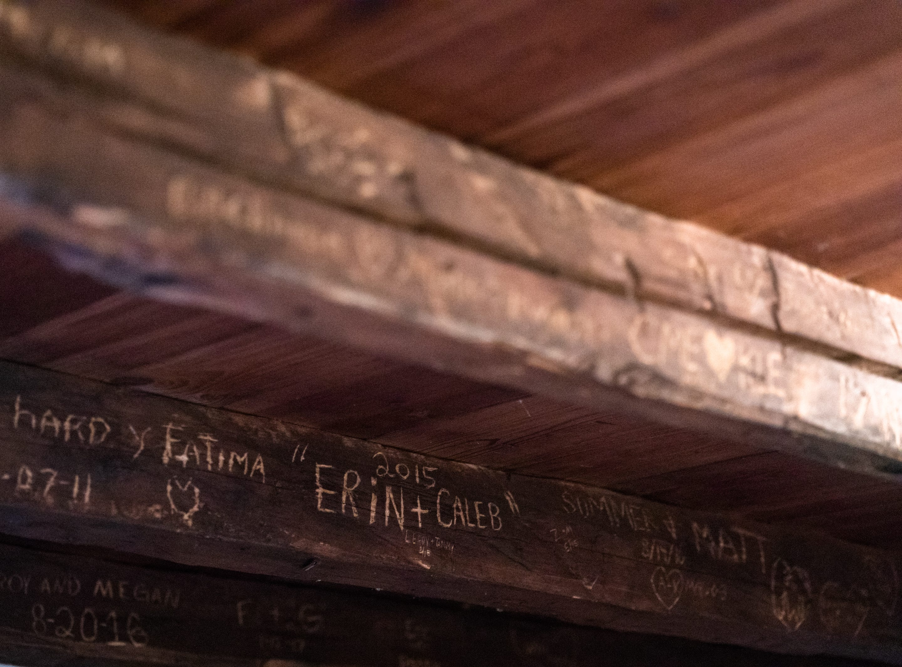 Visitors have left their marks on wooden beams in in Chris' Cabin, an original 1800's log cabin at the McLeod family's Asheville Cabins of Willow Winds vacation rentals in South Asheville off of Sweeten Creek Road.