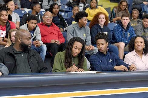 Roberson senior and Asheville Christian Academy transfer Caleb Mills is watched by family and friends as he signs to play basketball at the University of Houston during an early signing day ceremony at Roberson High School on Nov. 14, 2018.